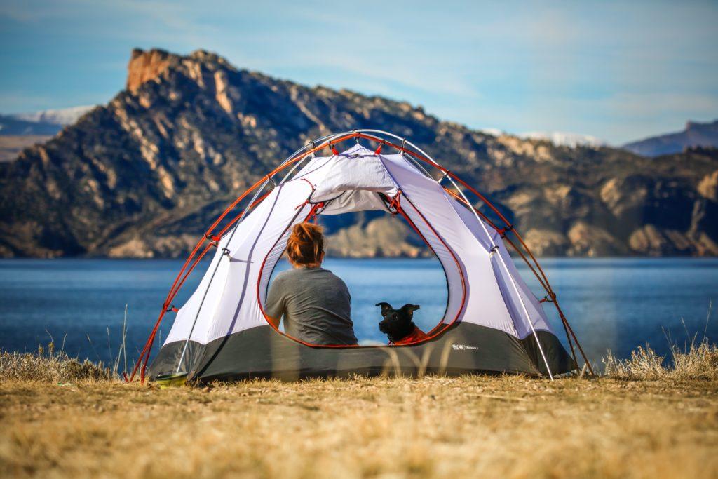 テントの中で休む女性と犬