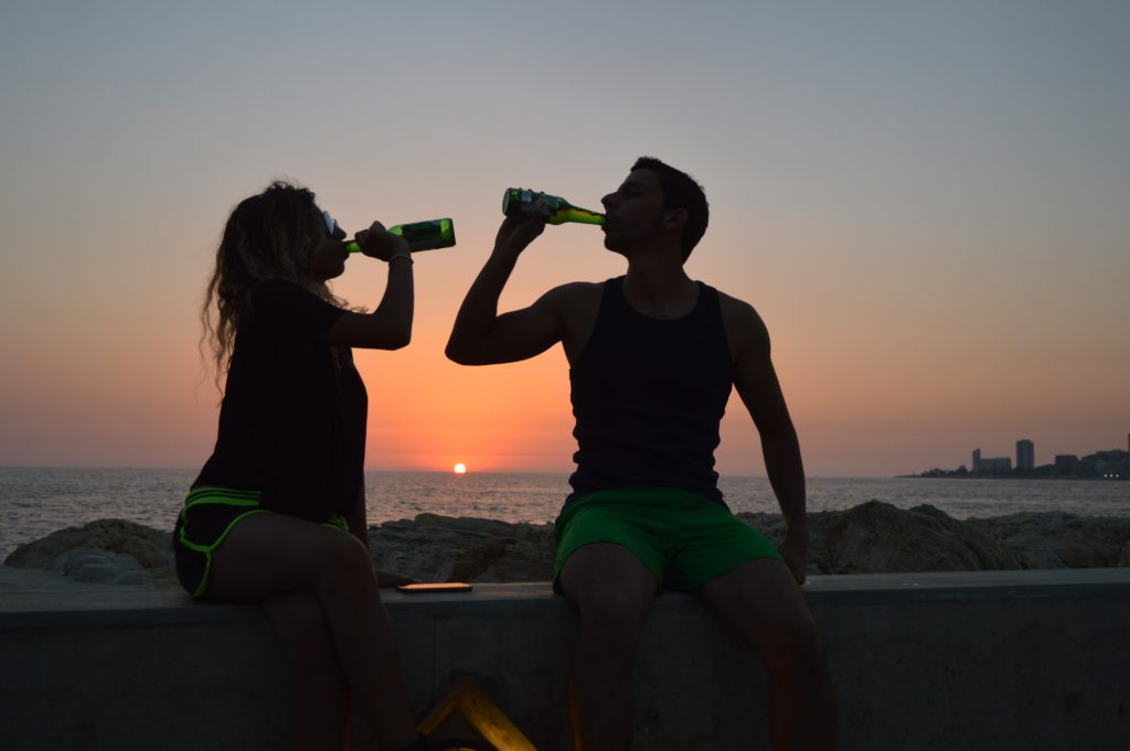 外で飲み物をのむ男女