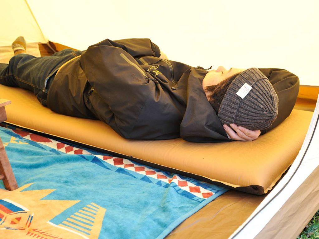 アウトドアマットで寝転ぶ男性